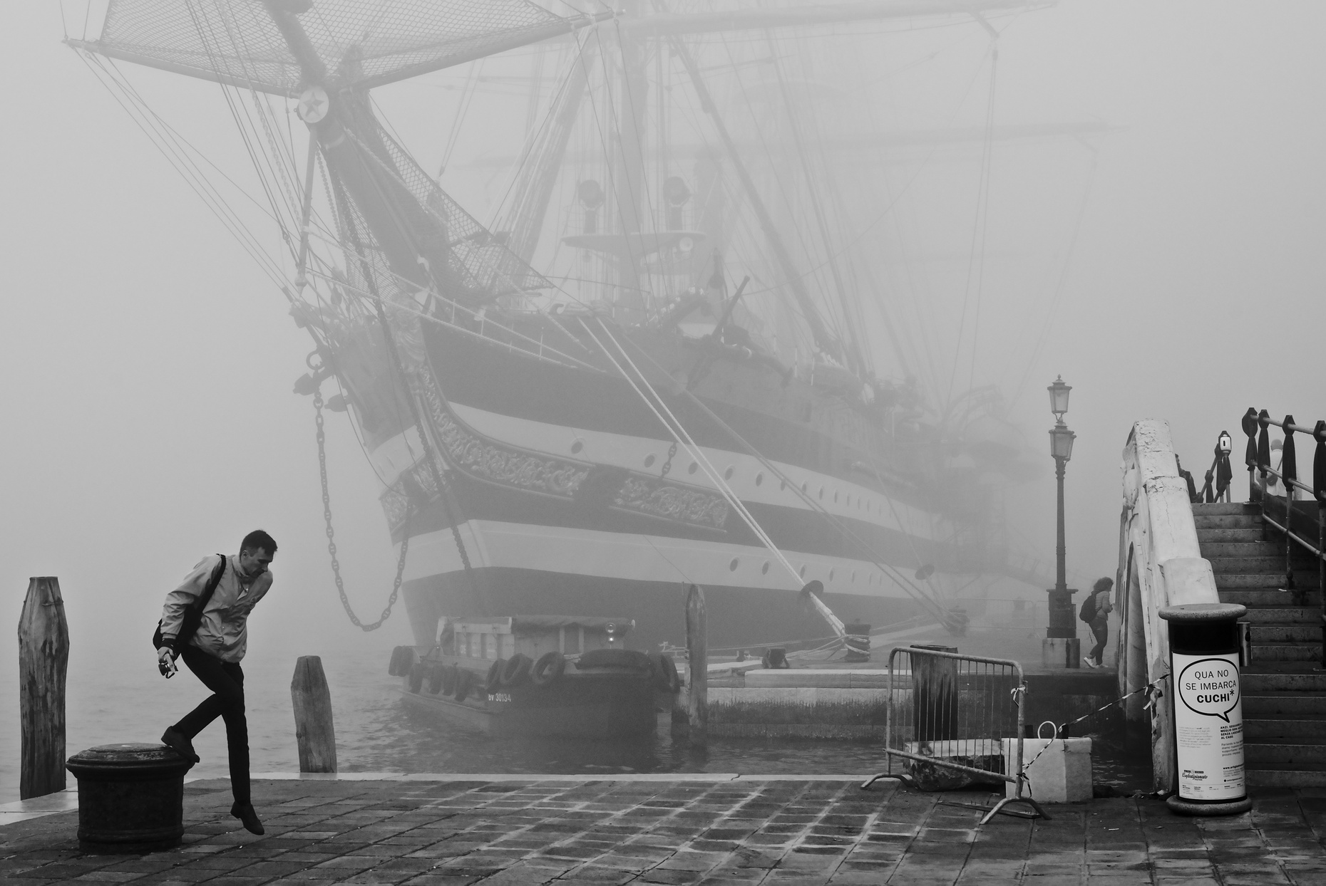 Tall ship Amerigo Vespucci in the morning fog in Venice, with man stepping down from mooring bitt in the foreground.