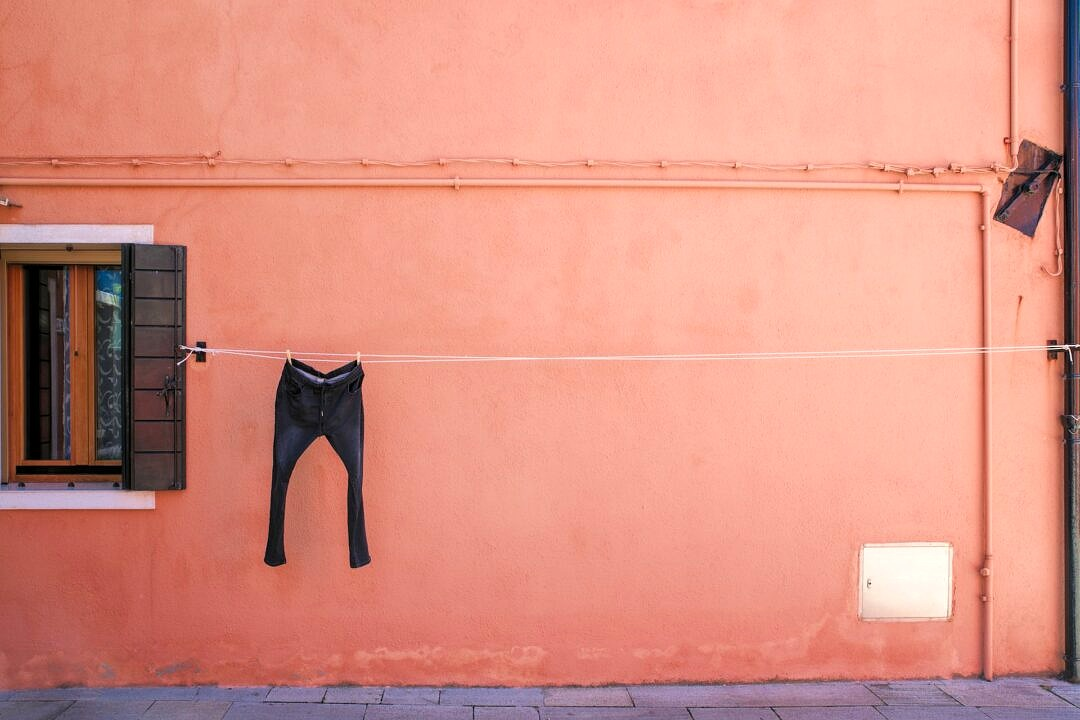 A pair of trousers drying on a line in front of an orange house